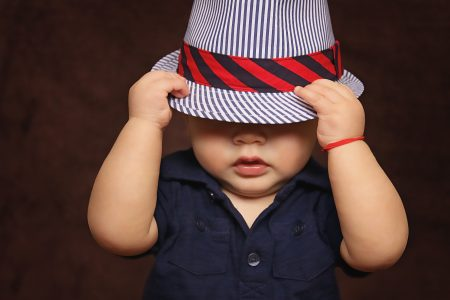 baby boy with hat covering face-capsule wardrobe for toddlers