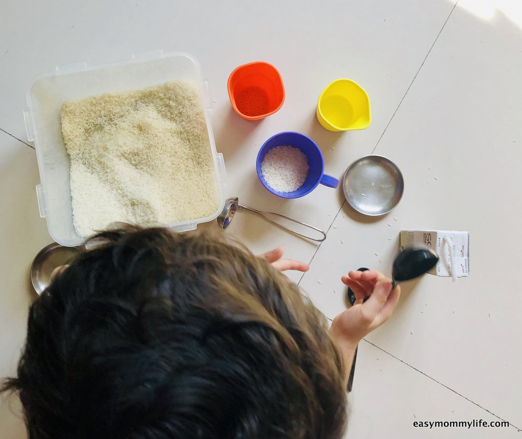 toddler playing with a sensory bin made of rice- indoor activities for toddler