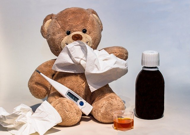 teddy bear with thermometer in hand and cough syrup in background