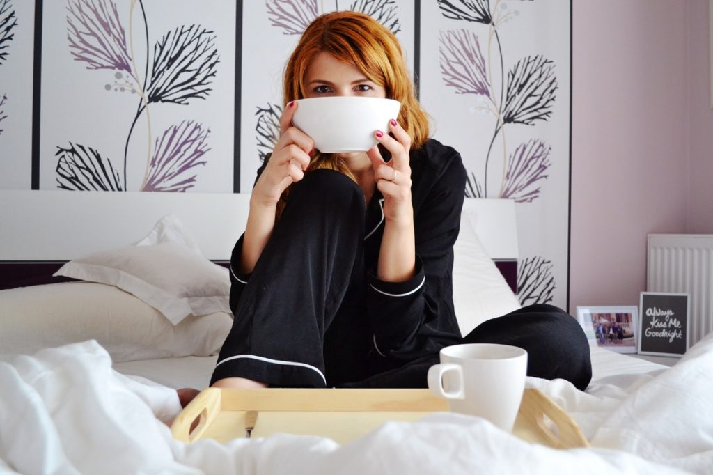 Woman in bed drinking coffee in her pajamas